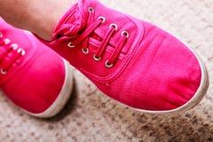 偶然充满活力的桃红色运动鞋特写镜头穿上鞋子在女性脚的起动 免版税库存图片