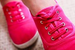 偶然充满活力的桃红色运动鞋特写镜头穿上鞋子在女性脚的起动 库存图片