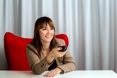 偶然典雅的女实业家在使用遥控的电视的办公室 免版税库存照片