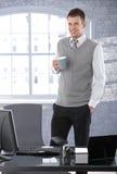 偶然在办公室微笑的生意人饮用的茶 库存照片