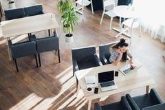 偶然地研究她的在咖啡馆的膝上型计算机的少妇 与一杯咖啡的乏味有吸引力的女性开会在工作 免版税库存照片