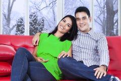 偶然夫妇坐红色沙发 库存图片
