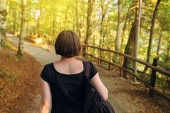 偶然女性走在有背包的秋天公园 免版税库存照片