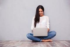 偶然妇女坐与膝上型计算机的地板 免版税图库摄影