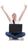 偶然妇女坐&与膝上型计算机的欢呼 免版税库存图片