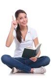 偶然妇女坐&读&有想法 免版税图库摄影