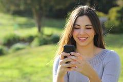 偶然妇女愉快使用一个巧妙的电话在公园 库存图片