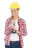 年轻偶然妇女藏品钻子和佩带安全帽。 免版税库存图片