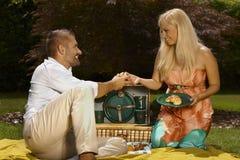 年轻偶然已婚夫妇有野餐在公园 免版税库存照片