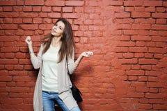 偶然布料的年轻美丽的愉快的妇女对砖墙 免版税库存图片