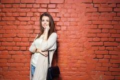 偶然布料的年轻美丽的愉快的妇女对砖墙 免版税库存照片