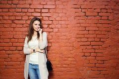偶然布料的年轻美丽的愉快的妇女对砖墙 库存照片