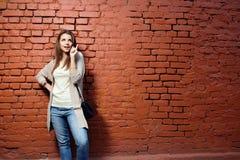 偶然布料的年轻美丽的愉快的妇女对砖墙 免版税图库摄影