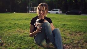偶然开会的美丽的少妇在与她狗宠物和微笑的草 与户外可爱的小犬座的所有者 股票录像