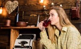 偶然成套装备的女孩在木葡萄酒内部坐 女孩行为似男孩的姑娘放松与玻璃用被仔细考虑的酒在房子里  免版税库存图片