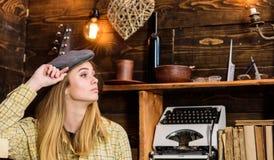 偶然成套装备的女孩有在木葡萄酒内部的平顶帽的 行为似男孩的姑娘概念 镇静面孔的夫人在格子花呢披肩衣裳看 免版税库存图片