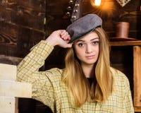 偶然成套装备的女孩有在木葡萄酒内部的平顶帽的 女孩行为似男孩的姑娘在猎场看手人房子里花费时间 行为似男孩的姑娘 图库摄影