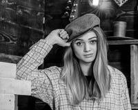 偶然成套装备的女孩有在木葡萄酒内部的平顶帽的 女孩行为似男孩的姑娘在猎场看手人房子里花费时间 行为似男孩的姑娘 免版税库存照片