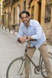 偶然时髦衣裳微笑的快乐的骑马的愉快的可爱的拉丁人在葡萄酒凉快的减速火箭的自行车 库存图片