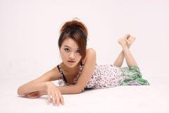 偶然服装的年轻中国夫人在地板上 库存照片