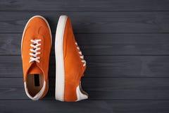 偶然橙色绒面革运动鞋顶视图在灰色木板条的 库存照片