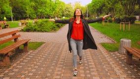 偶然灰色外套和色的运动鞋步行的妇女在城市 影视素材