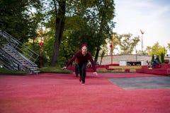 偶然的一个年轻人 自由流在做翻筋斗卷的都市城市,当跑时 库存照片