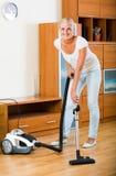 偶然的金发碧眼的女人使用在清洁期间的国内真空吸尘器 免版税库存照片