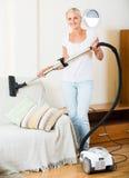 偶然的金发碧眼的女人使用在清洁期间的国内真空吸尘器 免版税库存图片