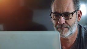 偶然精明的商人与便携式计算机一起使用在他的办公室 股票录像
