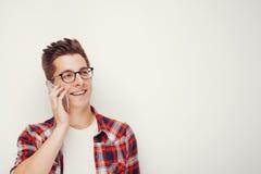 偶然红色衬衣的年轻学生谈话在智能手机 图库摄影