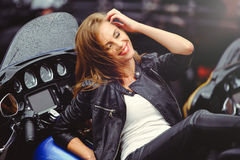 偶然美丽的妇女在街道明亮的微笑的一辆大摩托车说谎在一个晴天 免版税库存照片