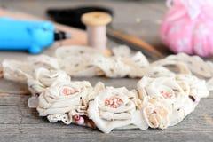 偶然花织品项链,胶合热的枪,剪刀,螺纹,针,在葡萄酒木桌上的毛毡 创造一条女性项链 免版税库存照片
