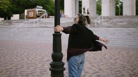 偶然,时髦的衣裳的一个愉快,无忧无虑的女孩是转动,跳舞在街道的一根柱子附近 微笑,快乐 股票录像
