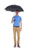 偶然年轻人在他的伞下 免版税库存照片