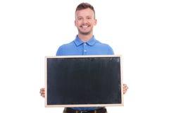 偶然年轻人拿着一个黑板 免版税库存照片
