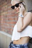 偶然年轻白肤金发的女孩谈话在电话 图库摄影