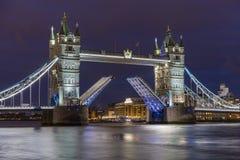 偶象伦敦塔桥在伦敦在晚上,美妙地被阐明和有被上升的平衡装置的 图库摄影