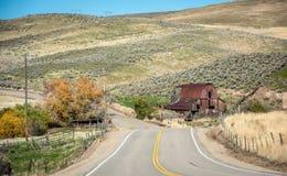 偶象谷仓在有秋天树和乡下公路的爱达荷 免版税库存图片