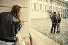偷偷靠近夫妇的Jelous妇女 库存照片