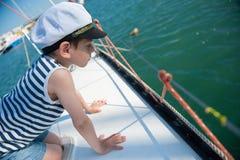 偷看在小船的边的上尉` s帽子的好奇英俊的小男孩 免版税库存图片