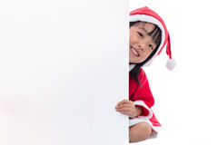 偷看在空白的委员会后的愉快的亚裔中国矮小的圣诞老人女孩 免版税图库摄影