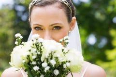 偷看在花束的新娘在庭院里 免版税图库摄影