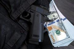 偷看在袋子口袋和金钱外面的手枪在背景中 免版税库存图片