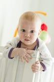 偷看在他的小儿床外面的好奇婴孩 图库摄影
