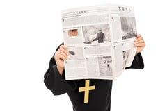 偷看通过在报纸的一个孔的鬼祟教士 免版税库存照片