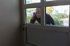 偷看通过玻璃门的人 库存照片