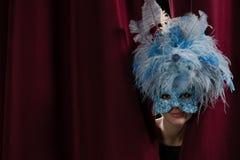 偷看通过红色帷幕的化妆舞会面具的女性艺术家 免版税库存图片