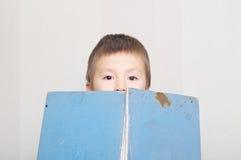 偷看从书、葡萄酒和旧书的男孩 免版税图库摄影