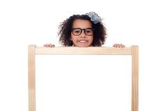 偷看从后面白色书写板的女孩 免版税库存图片